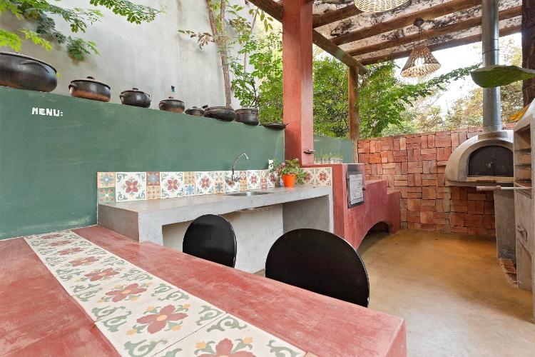 seixos para jardins campinas: parede de tijolinho tem forno de pizza e churrasqueira (à dir