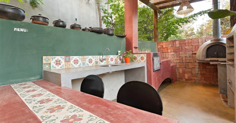 Projetada pela designer de interiores Fabiana Visacro, a cozinha externa possui fogão a lenha feito com tijolo refratário e revestido de cimento queimado. Além da peça, o espaço decorado com la