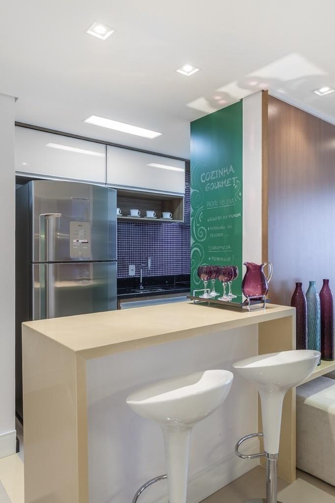 A arquiteta Marcy Ricciardi desenhou uma cozinha leve e descontraída para um apê compacto. Ao lado do balcão para refeições rápidas, o destaque fica é a parede pintada com tinta lousa. Acima da pia, as pastilhas dão cor ao ambiente
