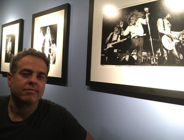 Marc Canter posa em frente a galeria de fotos feitas por ele em diversos shows dos anos 1980. Em primeiro plano, os Guns n' Roses em show de 1985. Ao fundo, Madonna e Eric Clapton