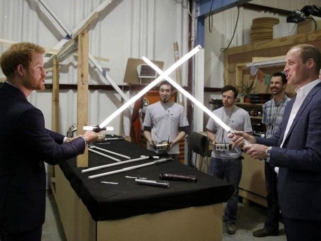 Os príncipes britânicos Harry (esq.) e William brincam com réplicas de sabres de luz em visita aos estúdios Pinewood