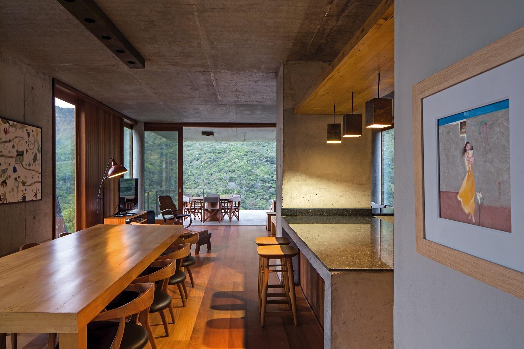 Desse ângulo vê-se a integração dos ambientes sociais com cozinha/bar e jantar em primeiro plano, seguidos por home theater, sala de estar e a generosa varanda de onde se vislumbra a bela paisagem. A Casa do Bomba, projetada pelo escritório Sotero Arquitetos, fica na Bahia