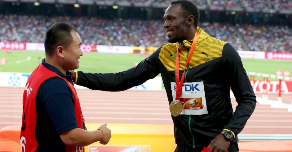Bolt sorri no reencontro com o cinegrafista chinês que o atropelou na quinta-feira