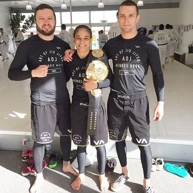 Livia Renata Souza posa com cinturão do Invicta FC ao lado dos irmãos Mendes