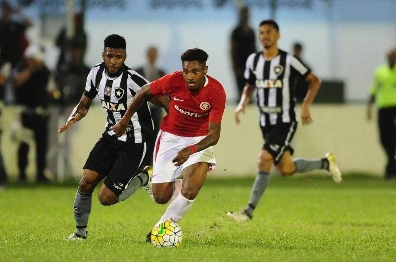 Vitinho tenta se livrar da marcação durante a partida entre Botafogo e Internacional