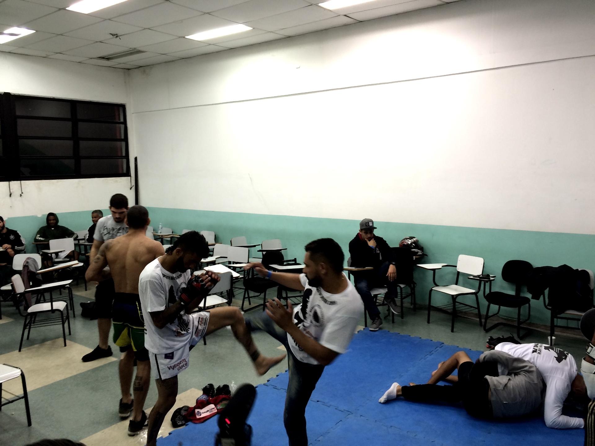 Lutadores de MMA fazem aquecimento em sala de aula de uma faculdade em São Paulo