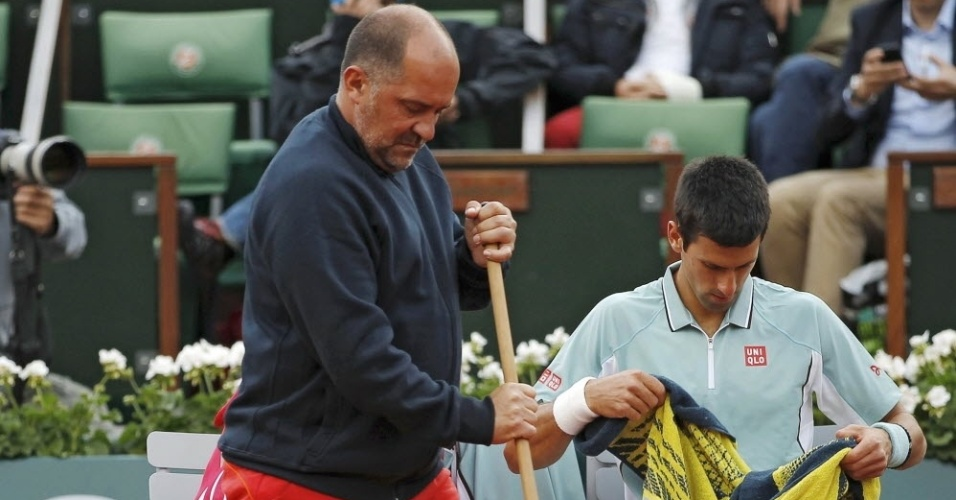 28.mai.2013 - Novak Djokovic descansa no intervalo da partida contra David Goffin, enquando árbitro varre a quadra em Roland Garros
