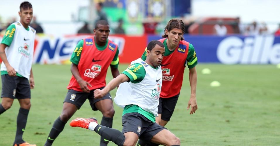 29.05.2013 - Observado de perto por Fernando e Filipe Luís, Lucas tenta um chute no primeiro trabalho com bola da seleção a caminho da Copa das Confederações