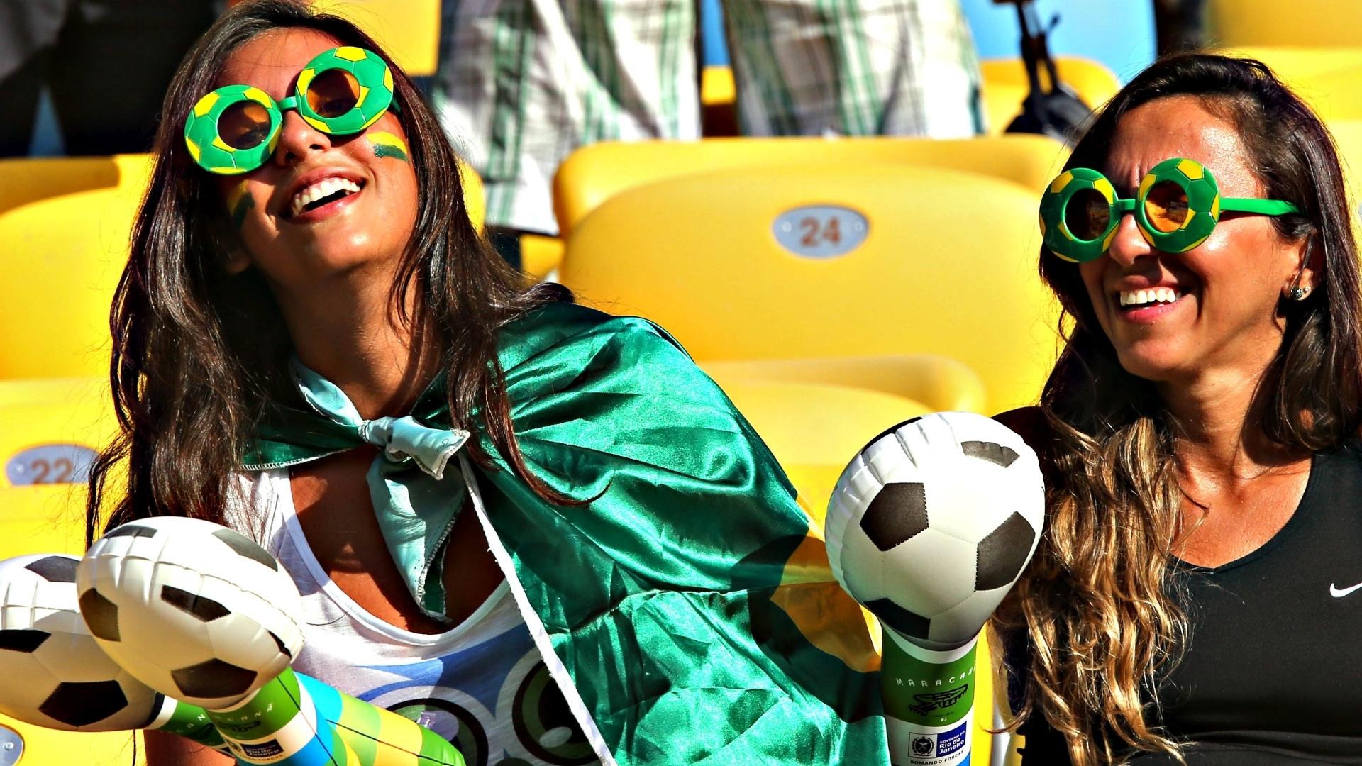 02.jun.2013 - Com rosto pintado e acessórios do Brasil, torcedora aguarda início da partida contra a Inglaterra no Maracanã