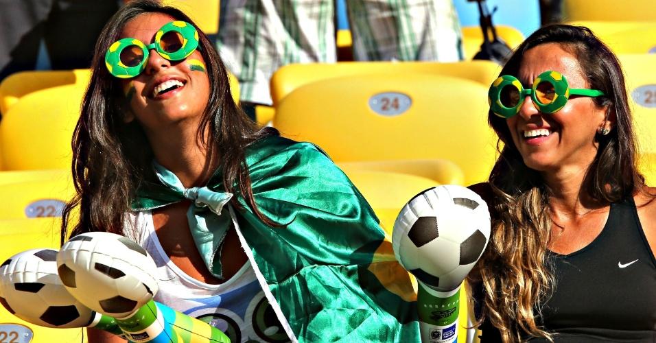 02.jun.2013 - Com rosto pintado e acessórios do Brasil, torcedora aguar