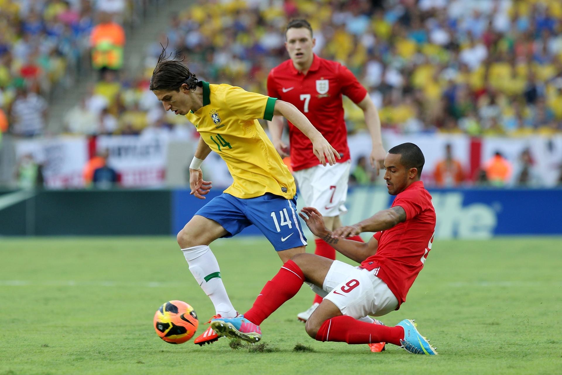 02.jun.2013 - Filipe Luis tenta fugir de carrinho de Theo Walcott na partida contra a Inglaterra no Maracanã