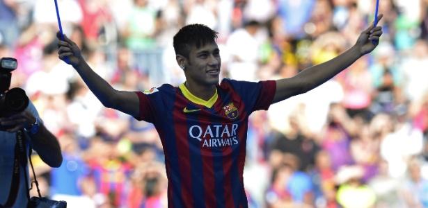 03.jun.2013 - Neymar acena com bandeiras do Barcelona na sua apresentação à torcida espanhola