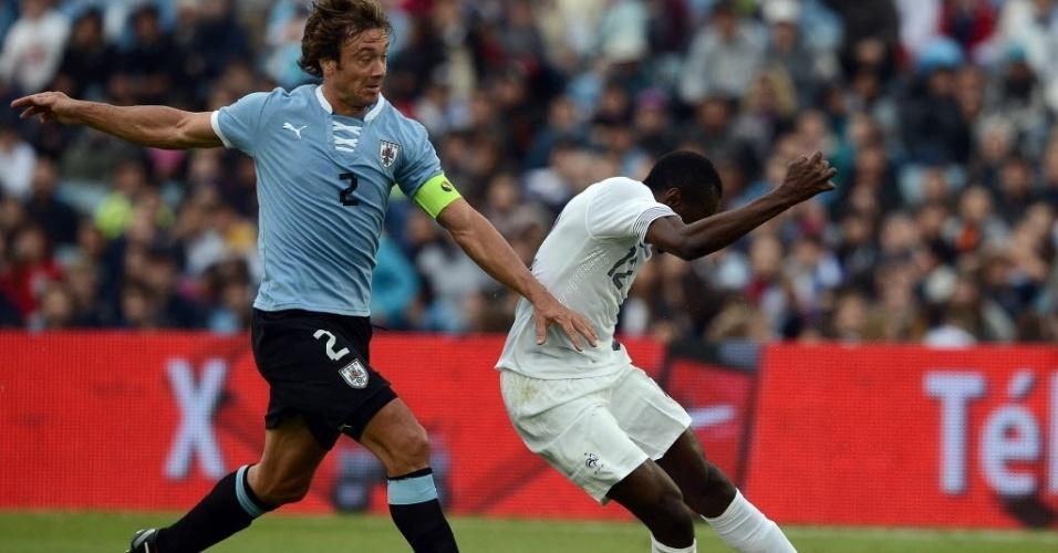 05.jun.2013 - Diego Lugano (esq.), zagueiro ex-São Paulo do Uruguai, disputa a bola com Matuidi, da França, em duelo amistoso entre as seleções