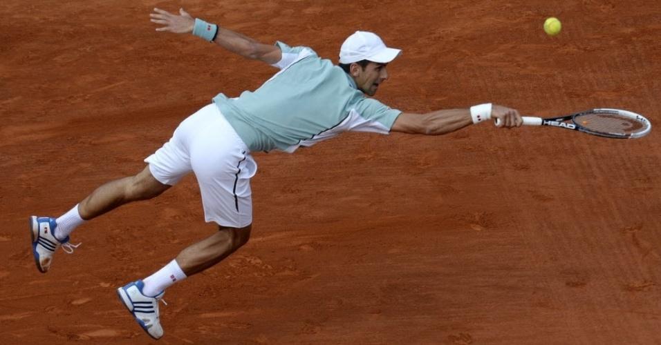05.jun.2013 - Djokovic se joga no saibro de Roland Garros durante disputa das quartas contra Tommy Haas