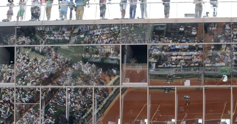 07.jun.2013 - Vidros na quadra central de Roland Garros refletem Novak Djokovic durante a semifinal contra Rafael Nadal