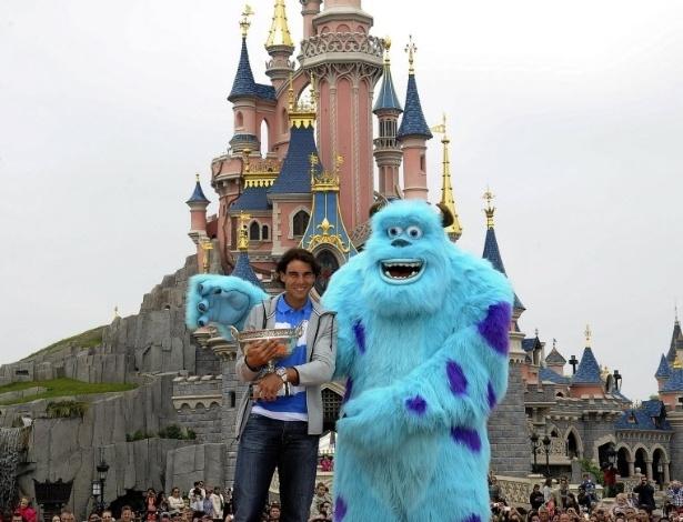 10.jun.2013 - Rafael Nadal posa ao lado de Sulley, personagem do filme Monstros S.A., na Eurodisney, em Paris, com seu troféu de Roland Garros