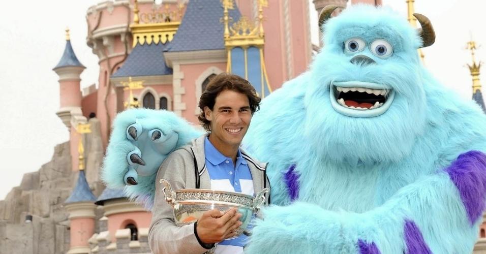 10.jun.2013 - Sulley, personagem do filme Monstros S.A.,  abraça Rafael Nadal, que levou seu troféu de Roland Garros para a Eurodisney, em Paris