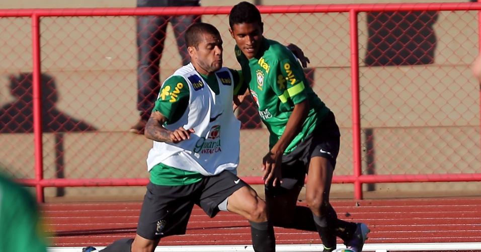 13.jun.2013 - Daniel Alves (esq.) e Paulinho disputam a bola durante treino da seleção brasileira nesta quinta-feira