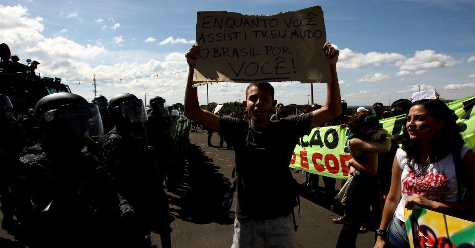 15.jun.2013 - Manifestante exibe cartaz durante protesto nos arredores do estádio Mané Garrincha