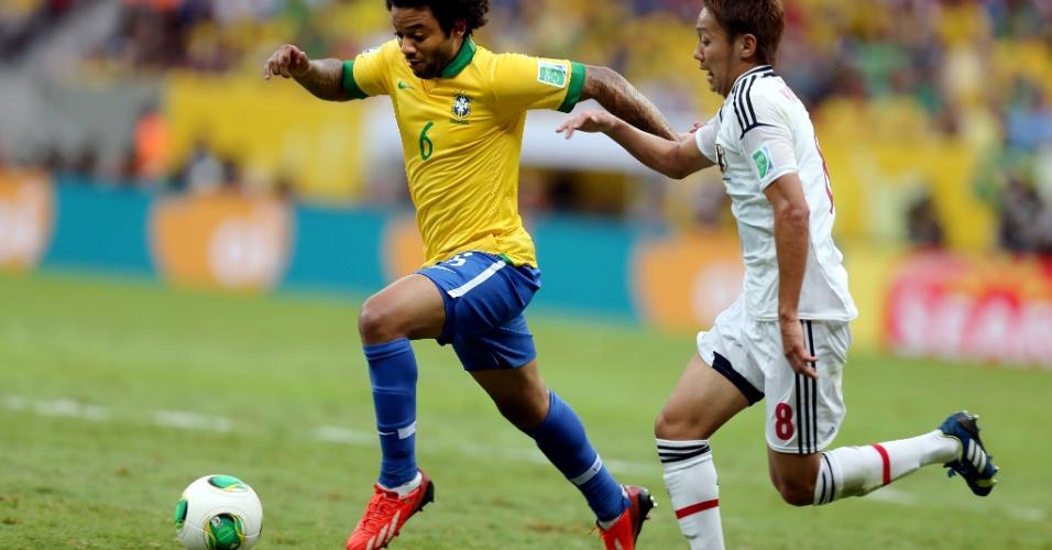 15.jun.2013 - Marcado de perto por japonês, Marcelo carrega a bola na abertura da Copa das Confederações
