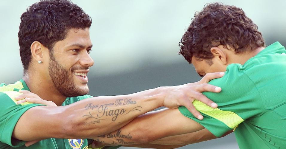 18.jun.2013 - Thiago Silva e Hulk fazem alongamento no campo em treino da seleção brasileira