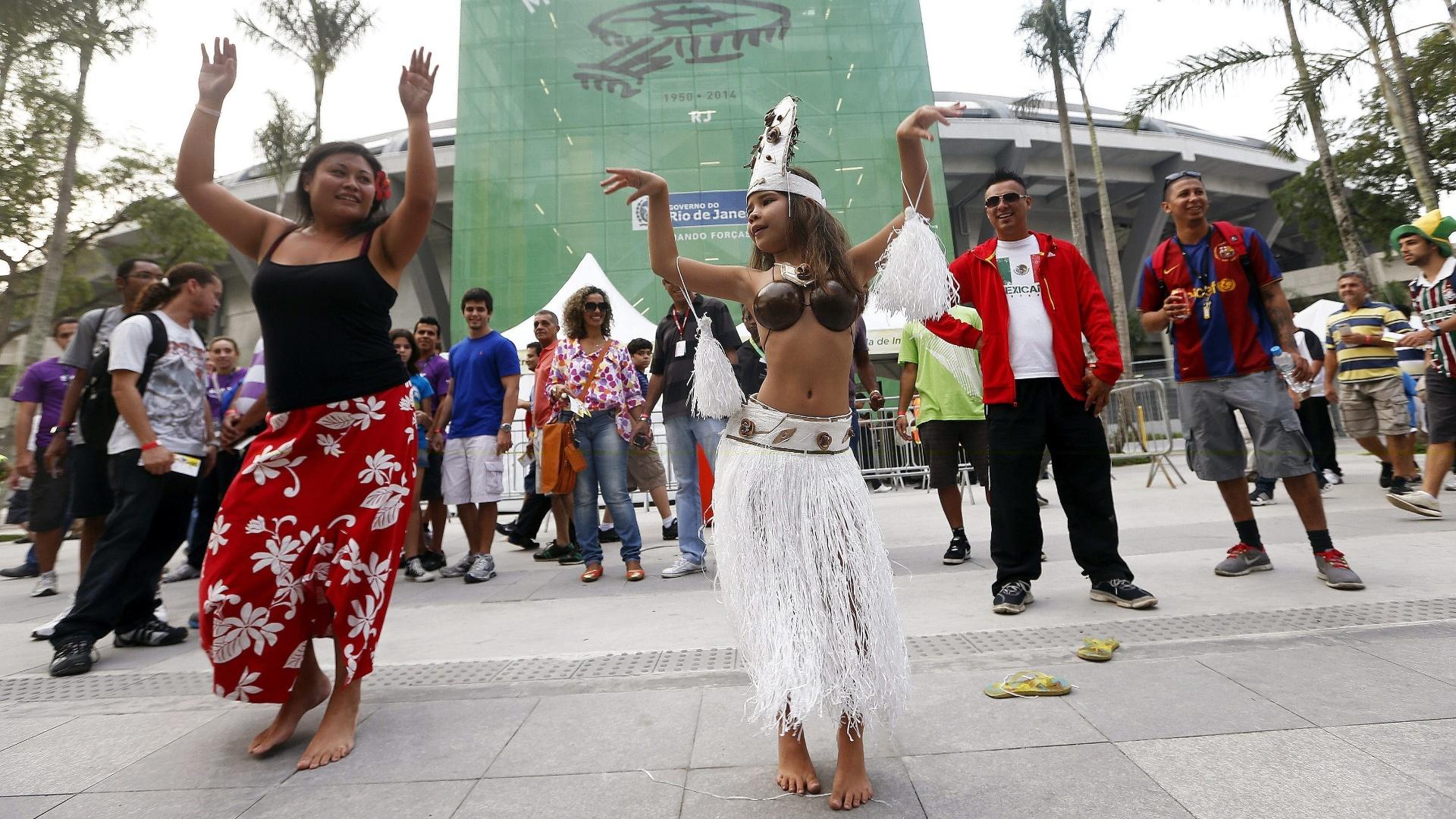 Torcedoras com roupa típica do Taiti dançam na porta do Maracanã antes da partida contra a Espanha