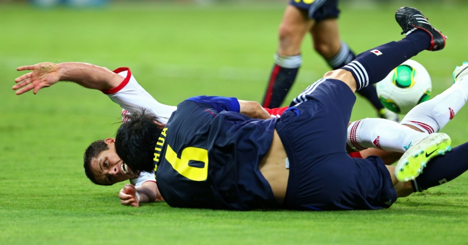 22.06.13 - Atsuto Uchida e Javier Hernandez caem no gramado após se chocarem na partida entre Japão e México pela Copa das Confederações