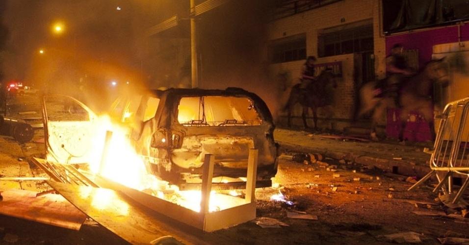 26.jun.2013 - Cavalaria passa por carro incendiado em confronto entre manifestantes e polícia próximo ao Mineirão
