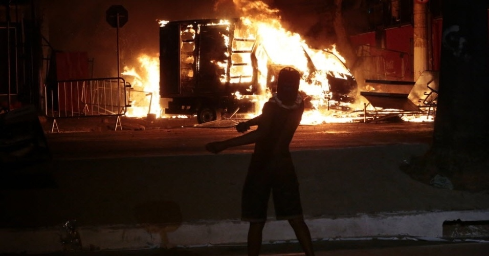 26.jun.2013 - Manifestante joga pedra contra a polícia e observa caminhão incendiado nos arredores do Mineirão