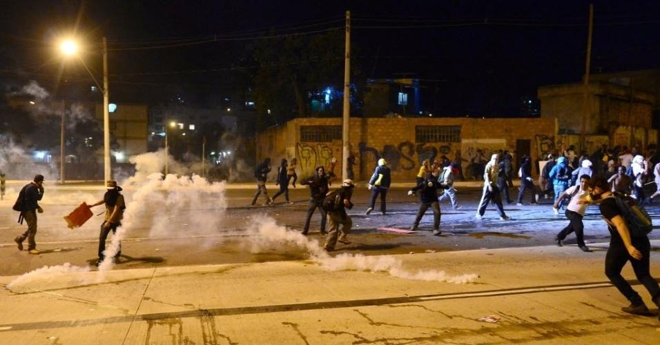 26.jun.2013 - Manifestantes correm de bombas de gás lacrimogêneo lançadas pela polícia em confronto nos arredores do Mineirão