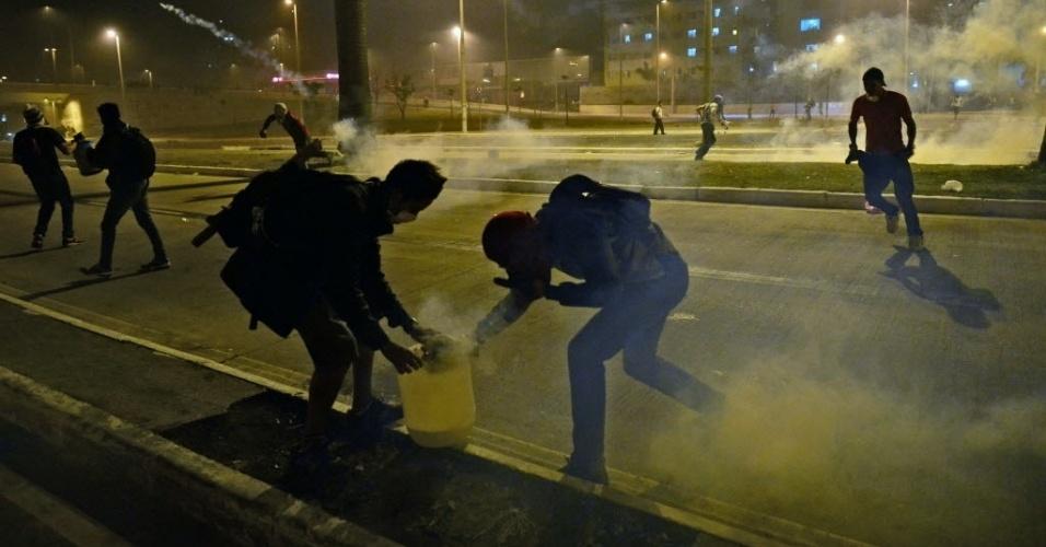26.jun.2013 - Manifestantes tentam se proteger de bombas de efeito moral lançadas pela polícia me confronto próximo ao Mineirão