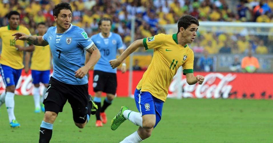 26.jun.2013 - Observado pelos uruguaios, Oscar parte com a bola dominada em lance da partida no Mineirão; Brasil venceu por 2 a 1 e se classificou para a final da Copa das Confederações