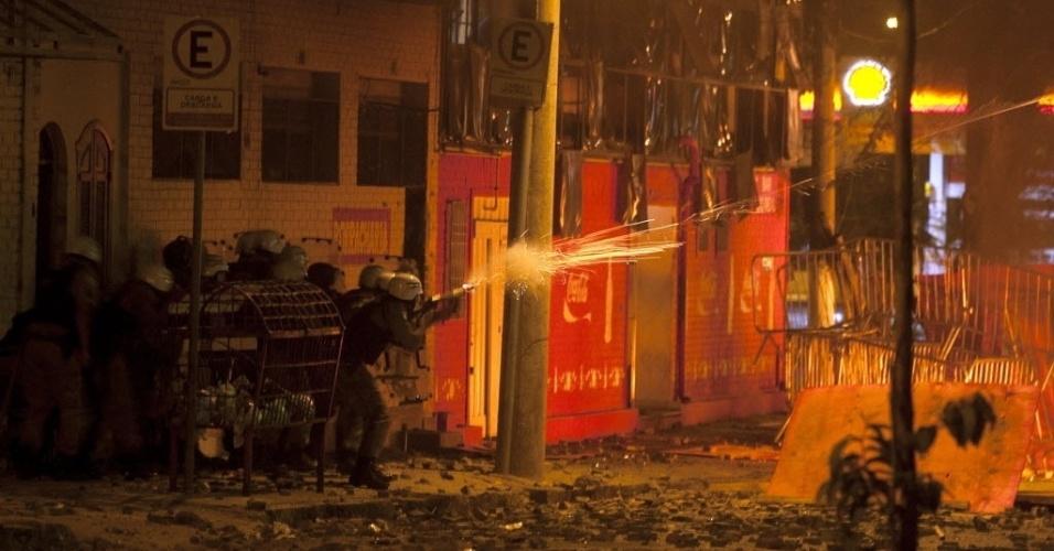 26.jun.2013 - Policial atira bala de borracha contra manifestantes em confronto nos arredores do Mineirão