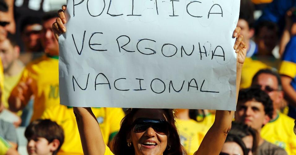 26.jun.2013 - Torcedora carrega cartaz de protesto dentro do Mineirão enquanto aguarda o início da partida entre Brasil e Uruguai