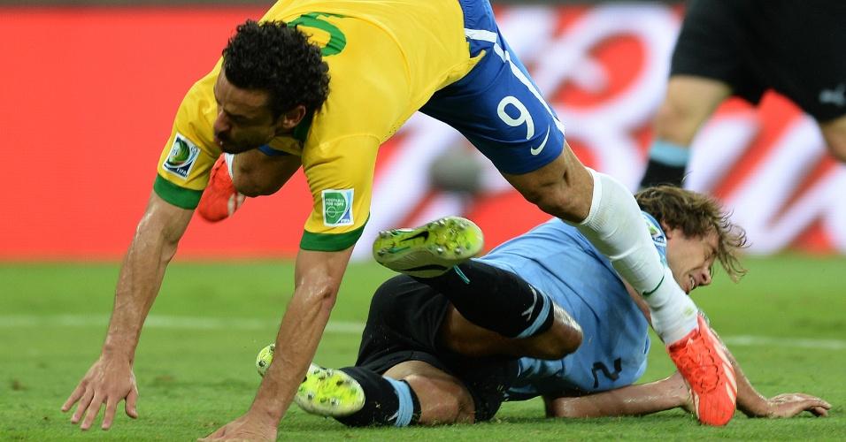 26.jun.2013 - Fred e Diego Lugano caem após disputa pela bola durante a vitória por 2 a 1 do Brasil sobre o Uruguai no Mineirão pela Copa das Confederações