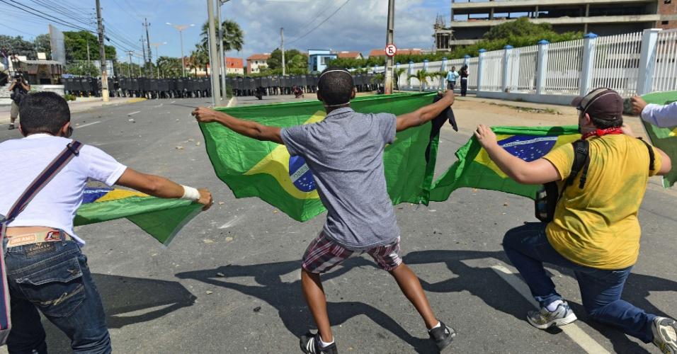 27.jun.2013 - Manifestantes esticam bandeiras do Brasil a metros de distância de barreira policial; o protesto pretende chegar ao estádio do Castelão, e a polícia tenta conter o avanço