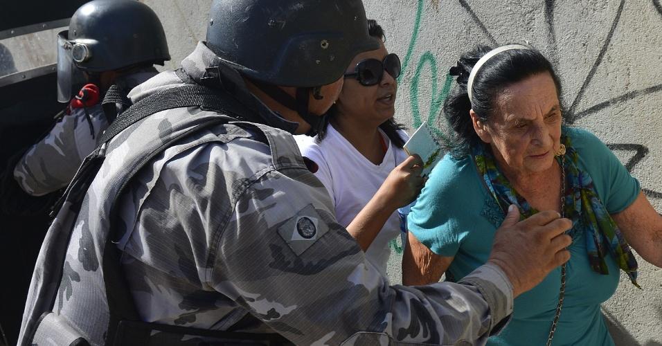 27.jun.2013 - Torcedores com ingressos para Espanha x Itália são ajudados por policiais a passarem barreira oficial montada para conter o avanço de manifestantes em direção ao Castelão