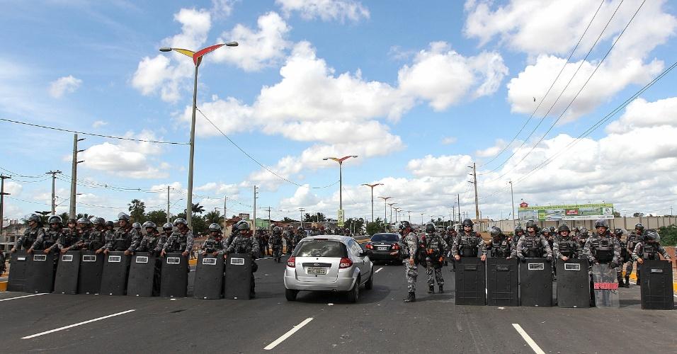 27.jun.2013 - Barreira policial formada no acesso ao Castelão abre espaço para a passagem de carro