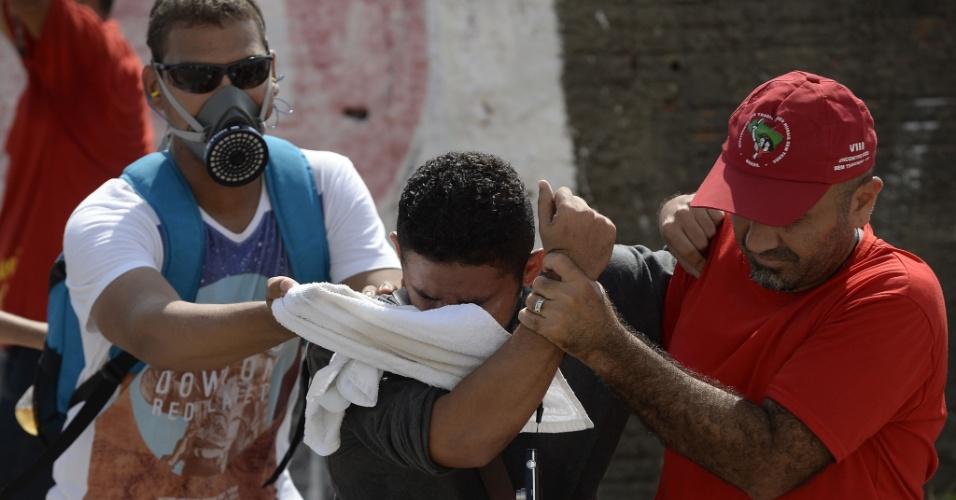 27.jun.2013 - Manifestantes se protegem dos efeitos das bombas de gás durante confronto com policiais em Fortaleza