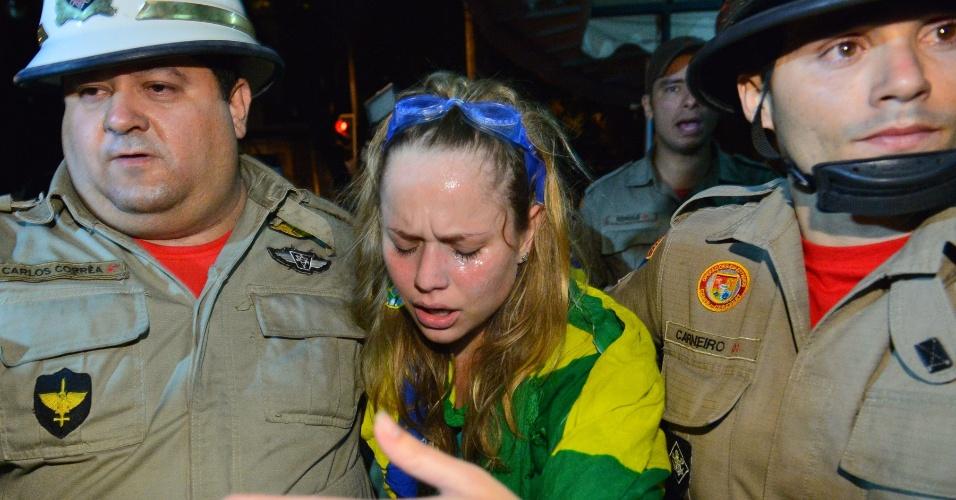 30.jun.2013 - Bombeiros amparam mulher afetada por gás lacrimogênio em protesto perto do Maracanã