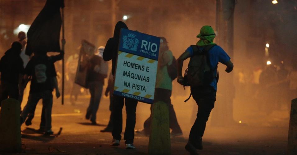 30.jun.2013 - Manifestantes correm em meio à fumaça com placa arrancada da rua
