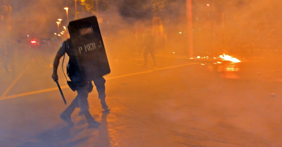 30.jun.2013 - Policial se protege de fogo ateado por manifestantes perto do Maracanã