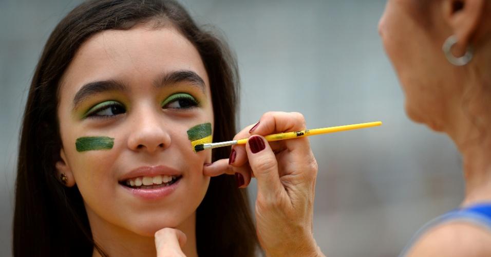 30.jun.2013 - Garota pinta o rosto antes de entrar no Maracanã para assistir à final da Copa das Confederações entre Brasil e Espanha