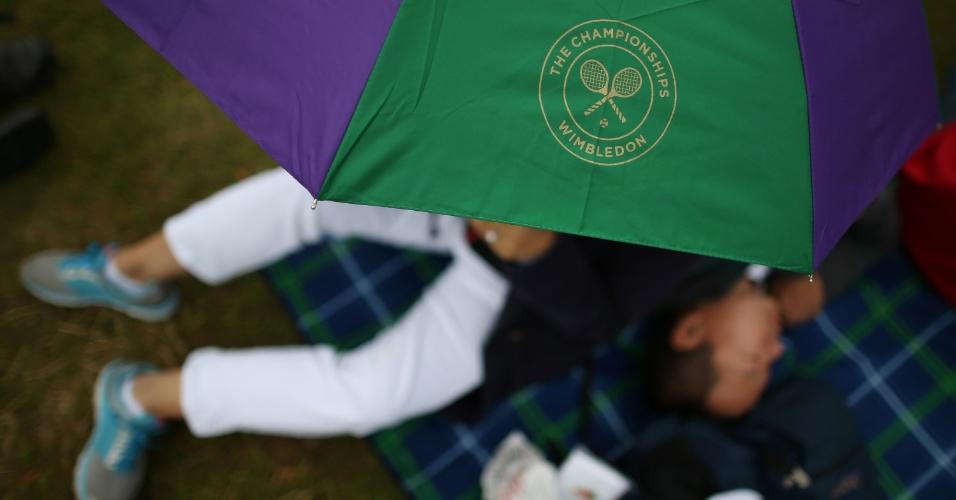 03.jul.2013 - Homem dorme embaixo de guarda-chuva com o logo de Wimbledon enquanto aguarda o início dos jogos no 10° dia do torneio