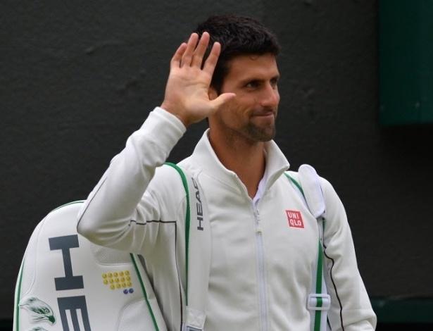 03.jul.2013 - Novak Djokovic acena para o público ao entrar em quadra para enfrentar Tomas Berdych nas quartas de Wimbledon