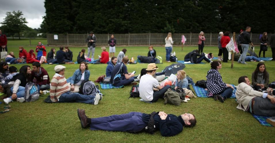 03.jul.2013 - Torcedor dorme enquanto outros sentam em gramado de Wimbledon esperando o início dos jogos no 10° dia de torneio