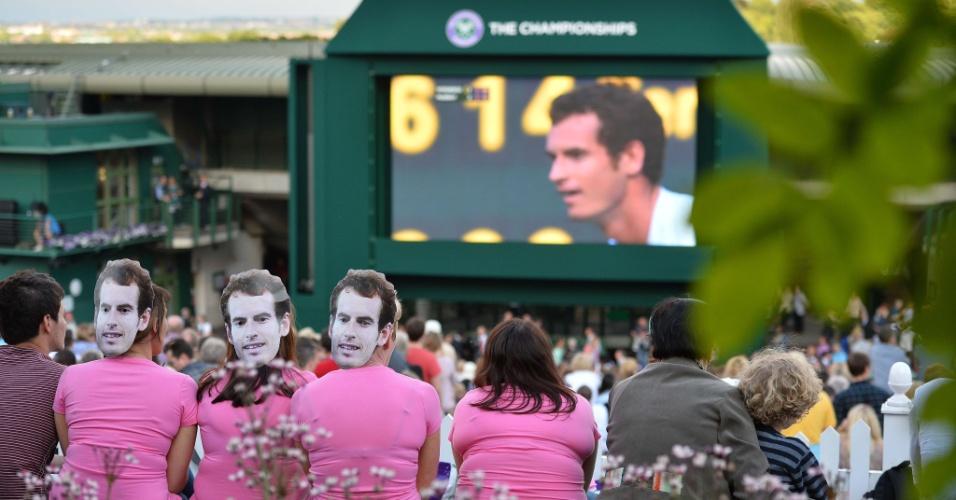 03.jul.2013 - Torcedores de máscara de Andy Murray acompanham a partida do tenista britânico contra Fernando Verdasco através de um telão do lado de fora da quadra