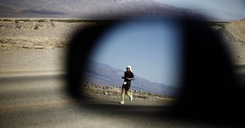 Espelho retrovisor de um automóvel reflete maratonista participando da corrida de 217 km no Vale da Morte (Death Valley), na Califórnia, nos EUA; prova é considerada a mais difícil do mundo por colocar os atletas em condições extremas, como temperaturas que chegam aos 55 graus Celsius
