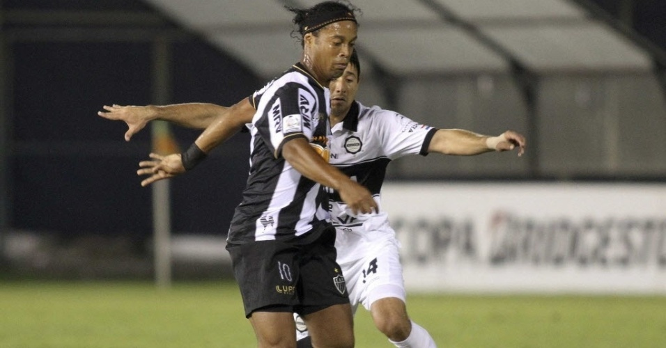 17.07.2013 - Ronaldinho Gaúcho recebe forte marcação de Eduardo Aranda, do Olímpia, durante a final da Libertadores, no Paraguai