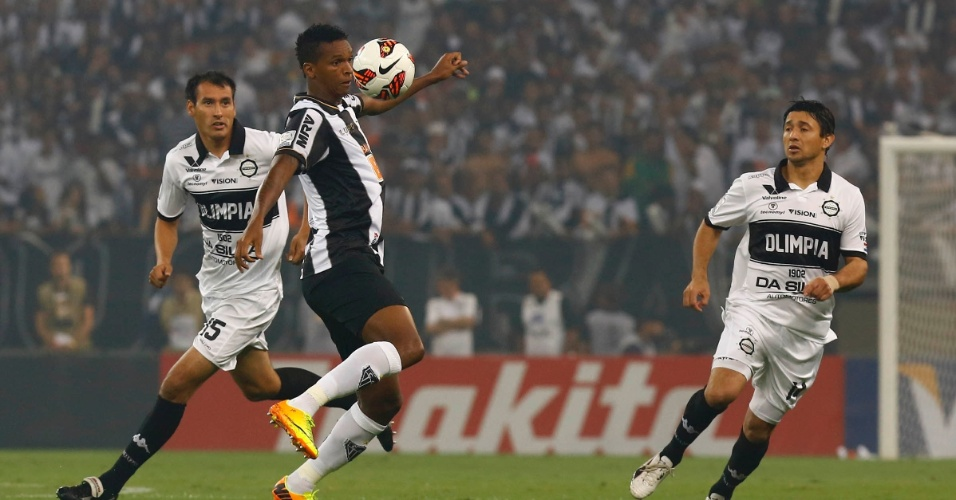 24.07.2013 - Jô domina a bola cercado por dois jogadores do Olimpia